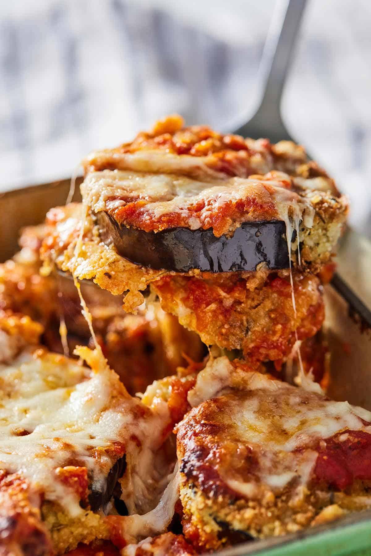 Close up of a spatula lifting up a serving of eggplant parmesan.