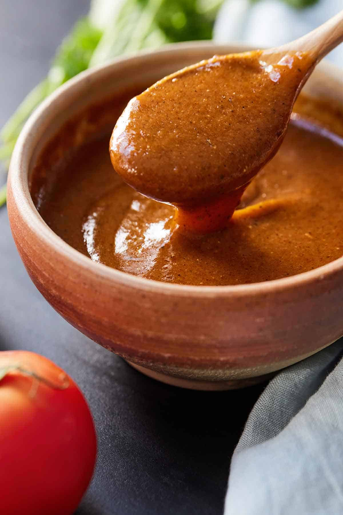 Enchilada sauce dripping off a wooden spoon in a bowl.