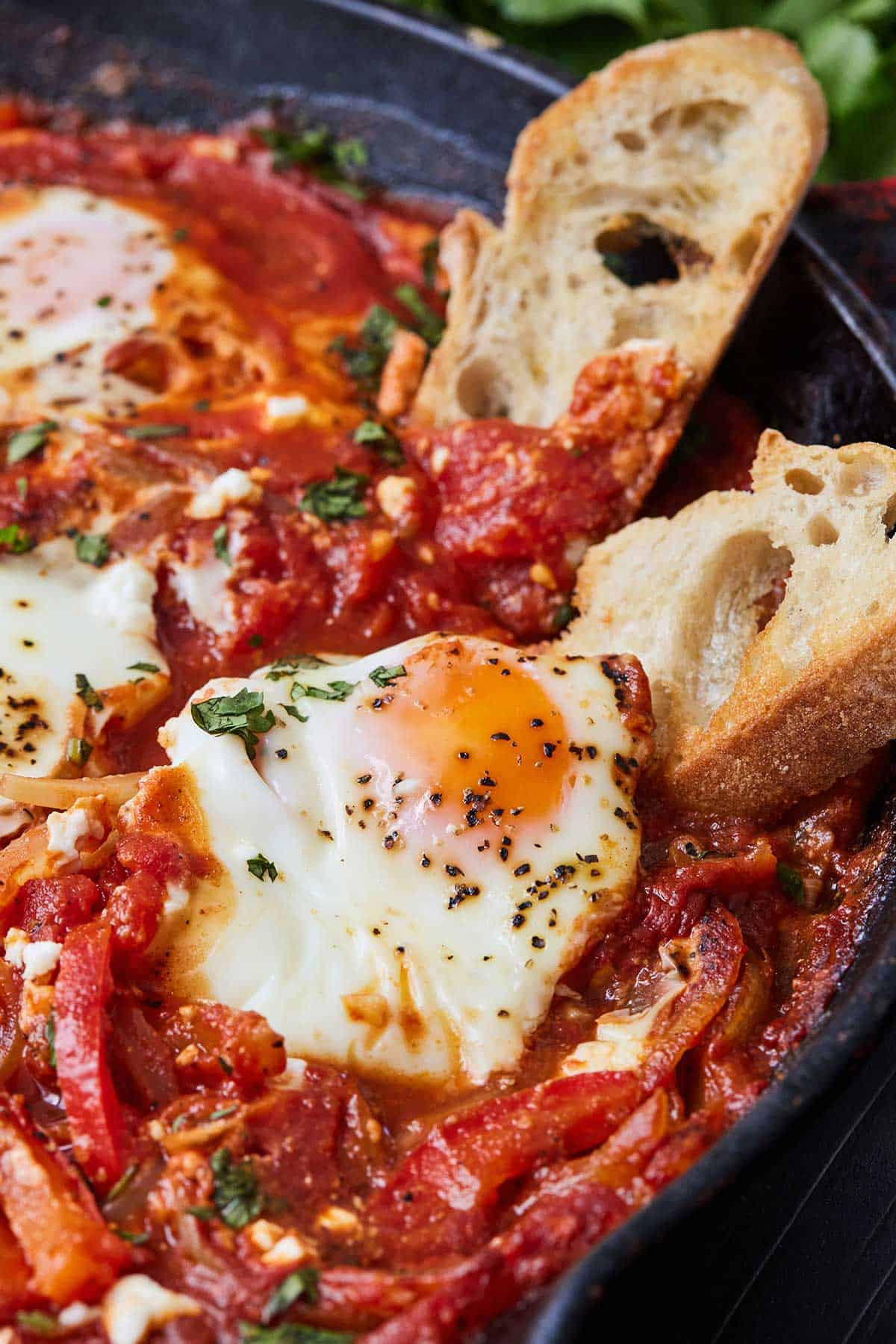 A pan of shakshuka with two pieces of bread dipped in the sauce beside an egg.