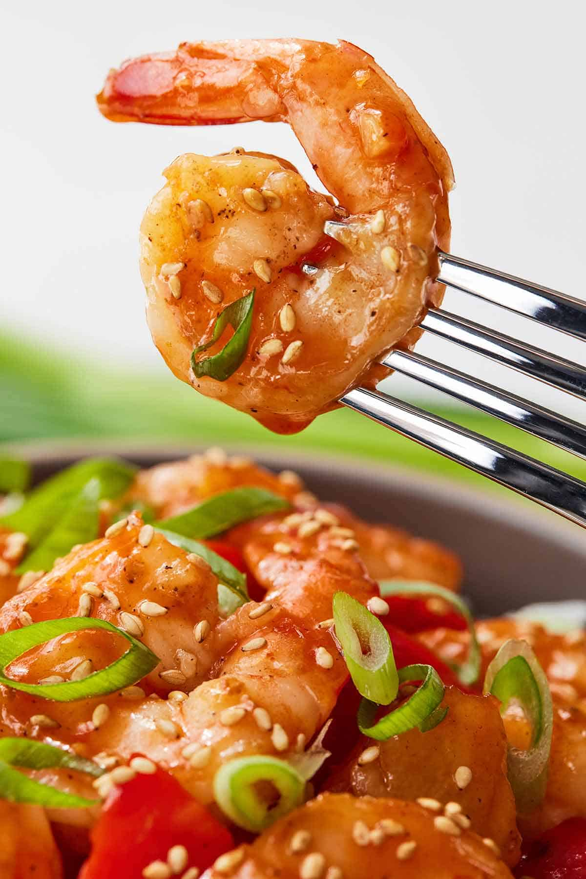 A fork holding up a single sweet and sour shrimp.