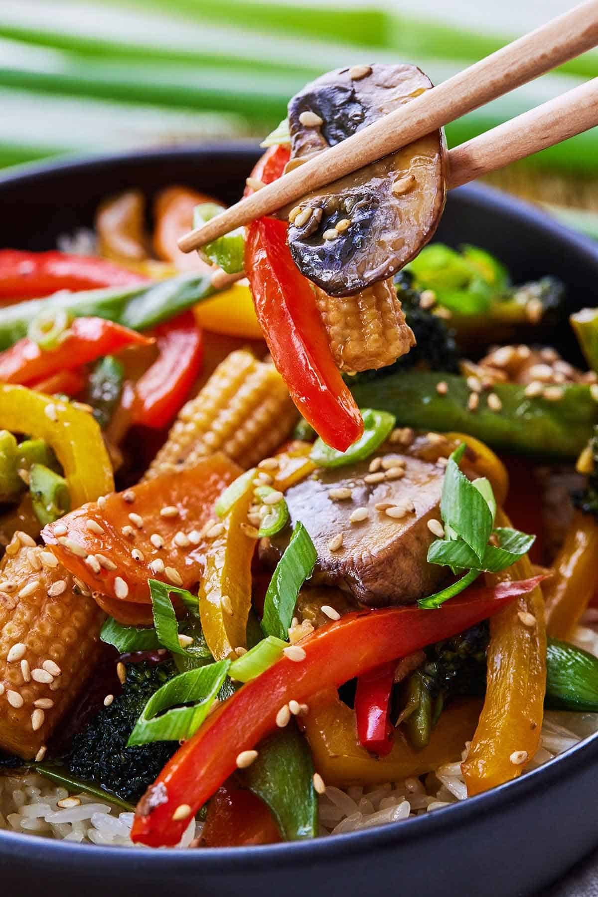 Close up of a chopstick lifting up mushrooms, bell pepper, and baby corn from a stir fry.