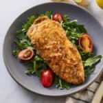 Chicken paillard in a plate over greens and tomatoes.