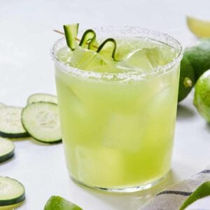 A glass of cucumber margarita with salt on the rim and a ribboned cucumber as garnish.