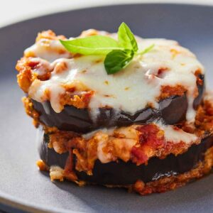 Close up of a serving of eggplant parmesan with melted cheese and basil on top.