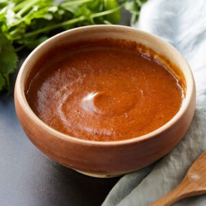 Red enchilada sauce in a bowl beside cilantro and a linen.
