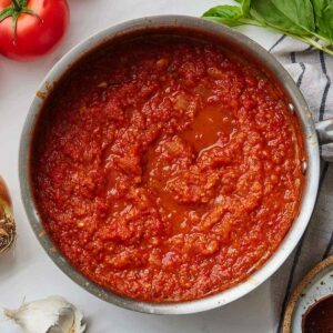 Close up of a pan of freshly made marinara sauce beside a linen and ingredients for the sauce.