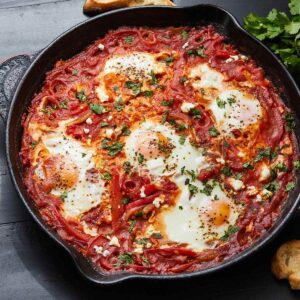 Cast iron skillet with shakshuka garnished with cilantro and feta cheese.