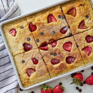 Close up of a sheet pan pancake beside a linen, strawberries, and chocolate chips.