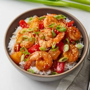Bowl of sweet and sour shrimp over top rice.