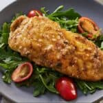 Pinterest graphic of chicken paillard over arugula and tomatoes.