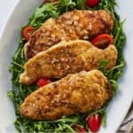 Pinterest graphic close up of chicken paillard on a platter of arugula and tomatoes.
