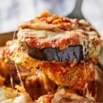 Pinterest graphic of a spatula lifting a serving of eggplant parmesan out of a dish.