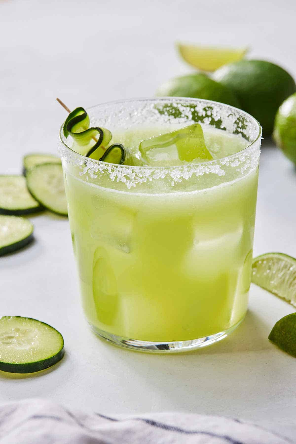 A glass of cucumber margarita with a salted rim and cucumbers slices around.