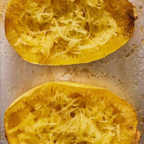 Two spaghetti squash on a sheet pan with the noodles pulled out.