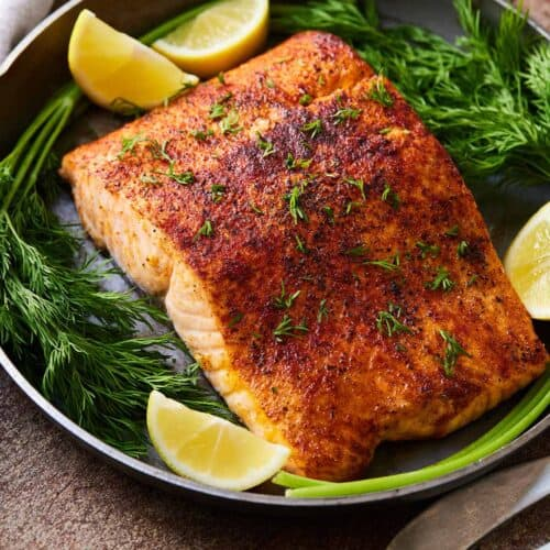 An air fryer salmon fillet on a plate to be served with garnishes.