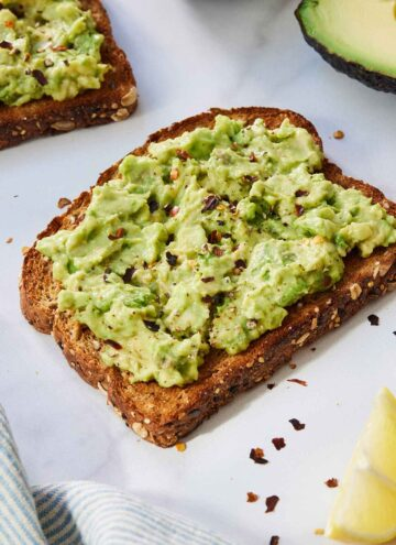 A slice of avocado toast with red chili flakes on top
