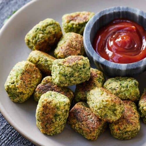 Broccoli tots in a plate with ketchup beside it.