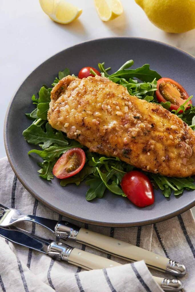 A plate of chicken paillard over arugula and tomatoes.