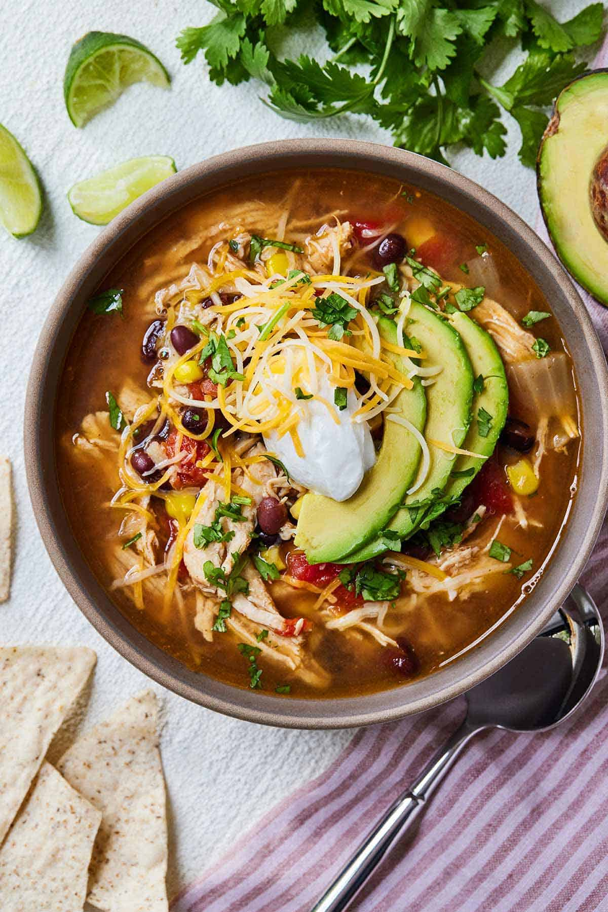 Overhead view of a bowl of Instant Pot chicken tortilla soup topped with shredded cheese, sour cream, and avocado and chips, limes, and cilantro on the table.