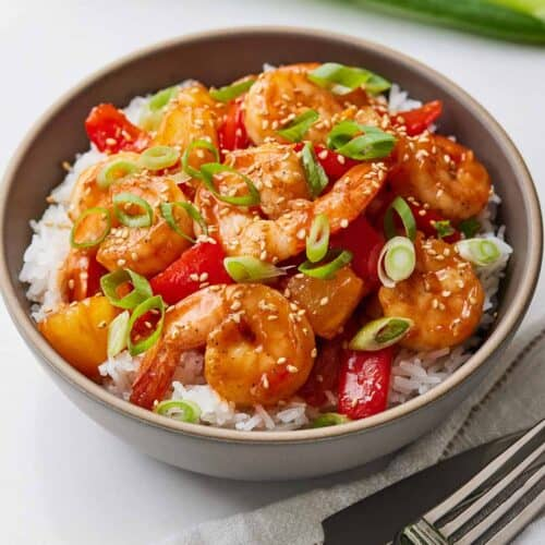 A bowl of sweet and sour shrimp over rice.