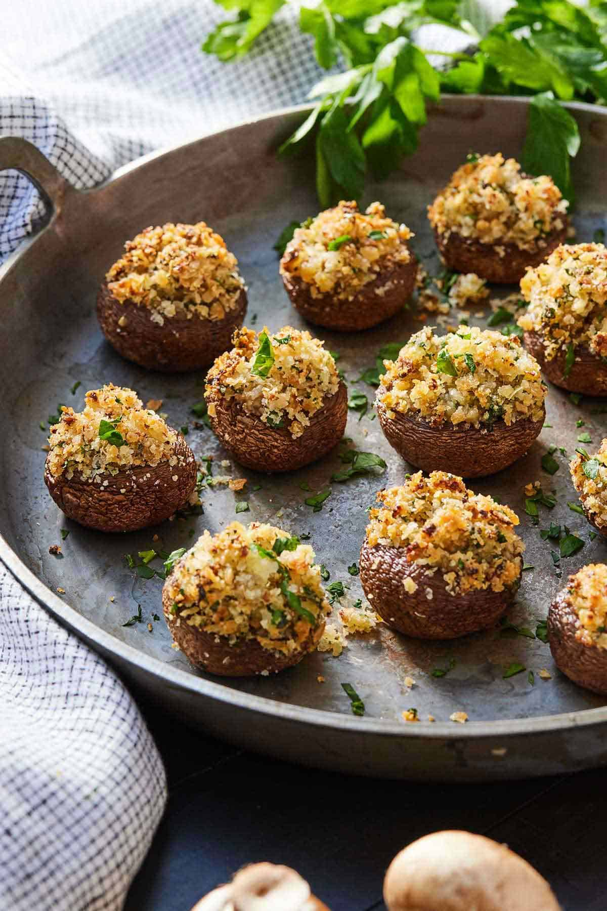 A platter of mushrooms that are stuffed with onions, garlic, breadcrumbs, cheese, and herbs.