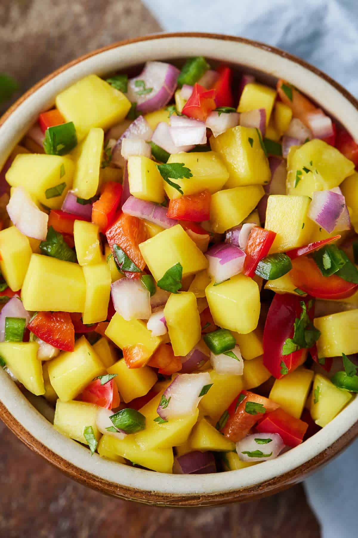 Overhead photo of a bowl of salsa with mango, tomatoes, onions, bell peppers, and jalapeno.