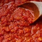 Pinterest graphic of the close up of marinara sauce with a wooden spoon stirring.