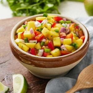 A bowl of mango salsa on a wooden serving board beside lime wedges and herbs.