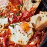 Pinterest graphic of shakshuka in a pan with bread dipped into the sauce.