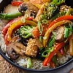 Pinterest graphic of veggie stir fry over rice with sesame seeds and green onion garnish.