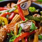 Pinterest graphic of a close up of chopsticks holding up mushrooms, bell pepper, and baby corn.