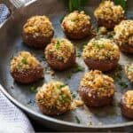 Pinterest graphic of a large grey platter with multiple stuffed mushrooms topped with fresh parsley.