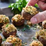 Pinterest graphic of a platter of stuffed mushrooms with one being lifted up.