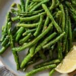 Pinterest graphic of an overhead view of air fryer green beans with a lemon wedge on the side.