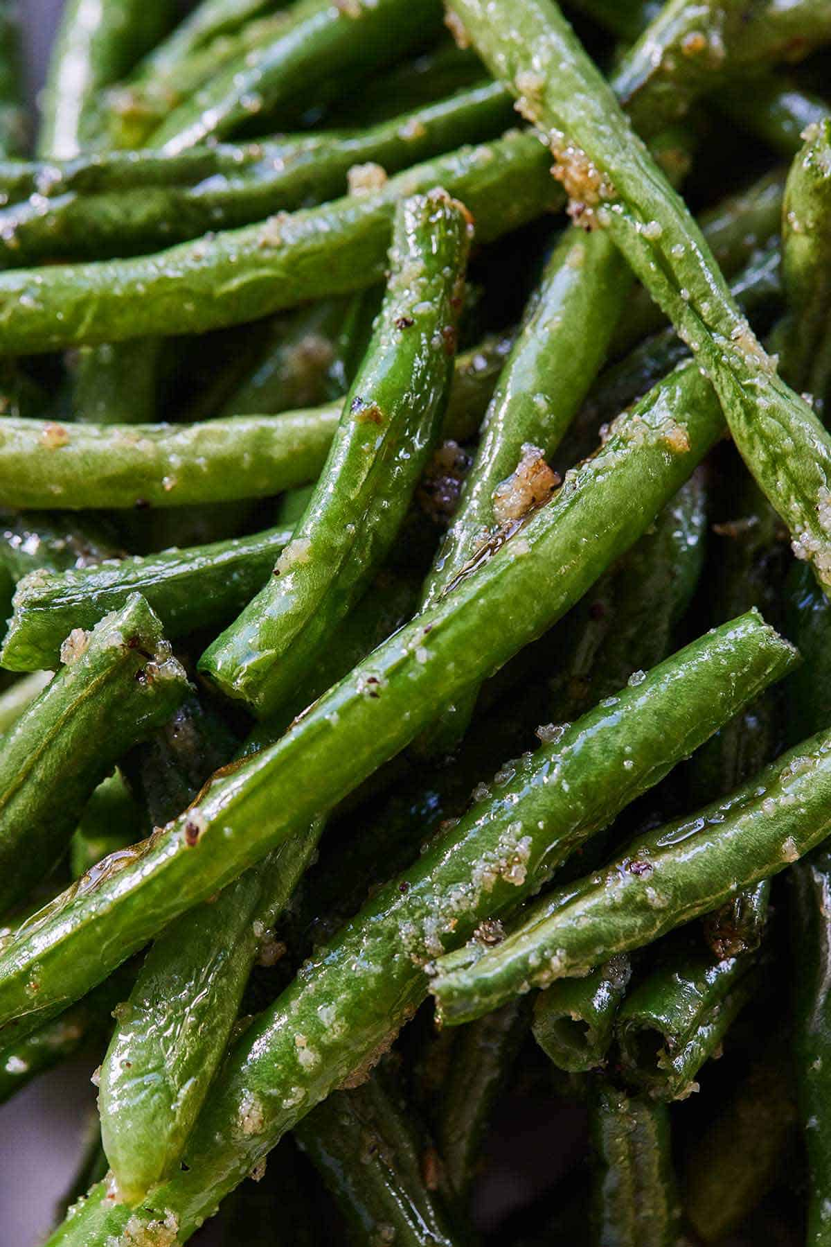 Close up of air fryer green beans, with garlic powder, salt, and pepper on it.