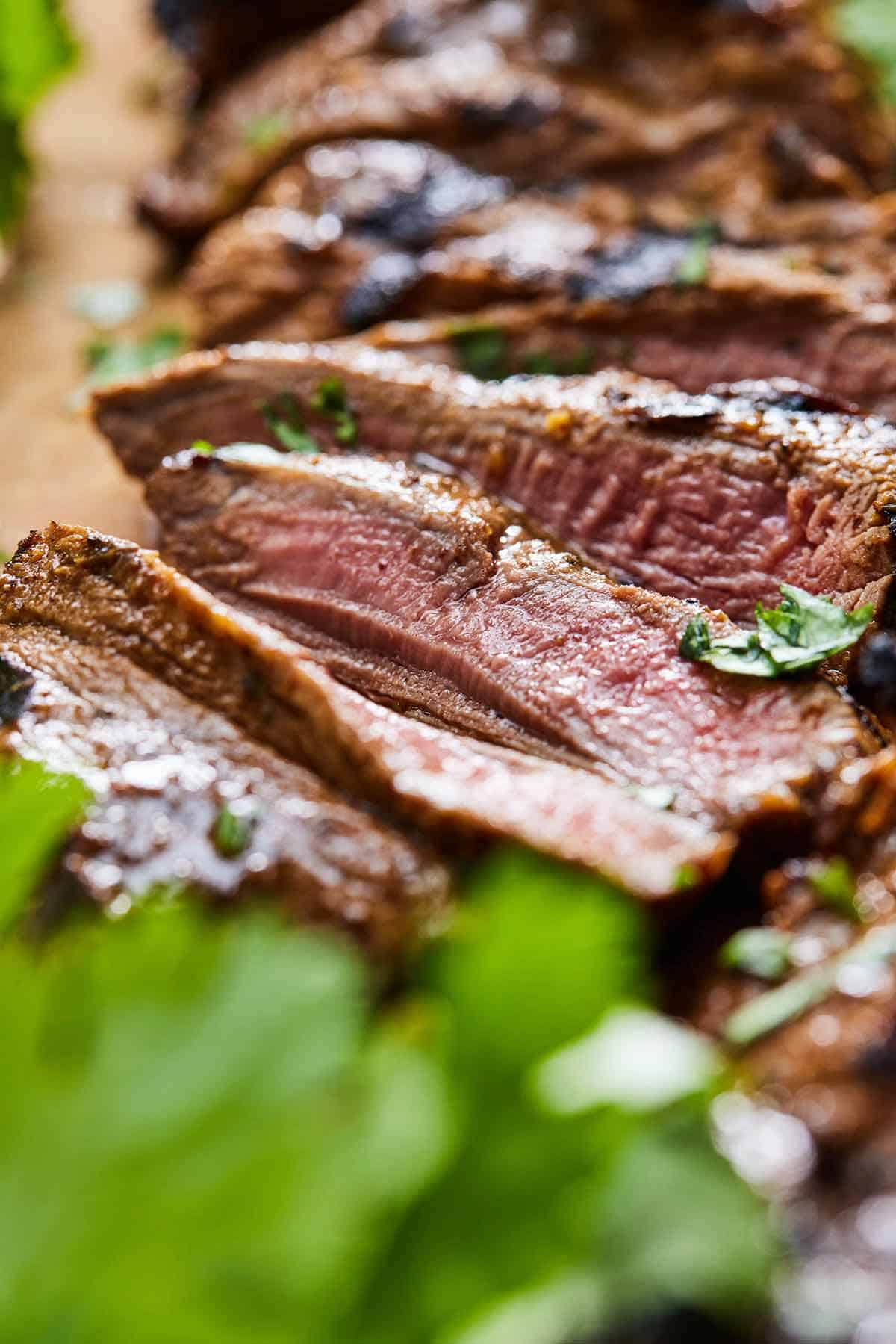 Close up photo of a slice of carne asada in focus, highlighting the piece being medium-rare.
