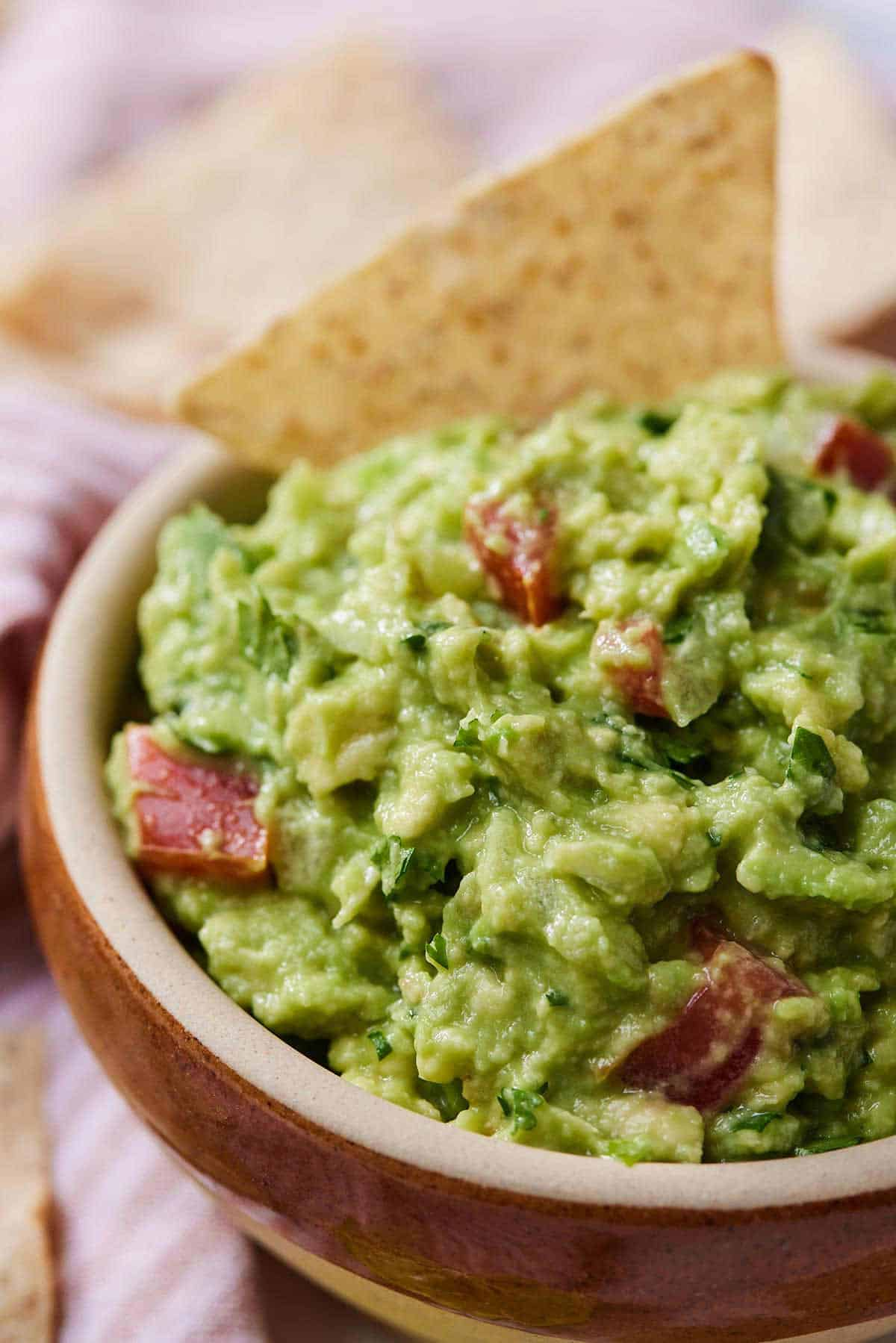 An angled image of a bowl of guacamole with a tortilla chip inside of the dip.