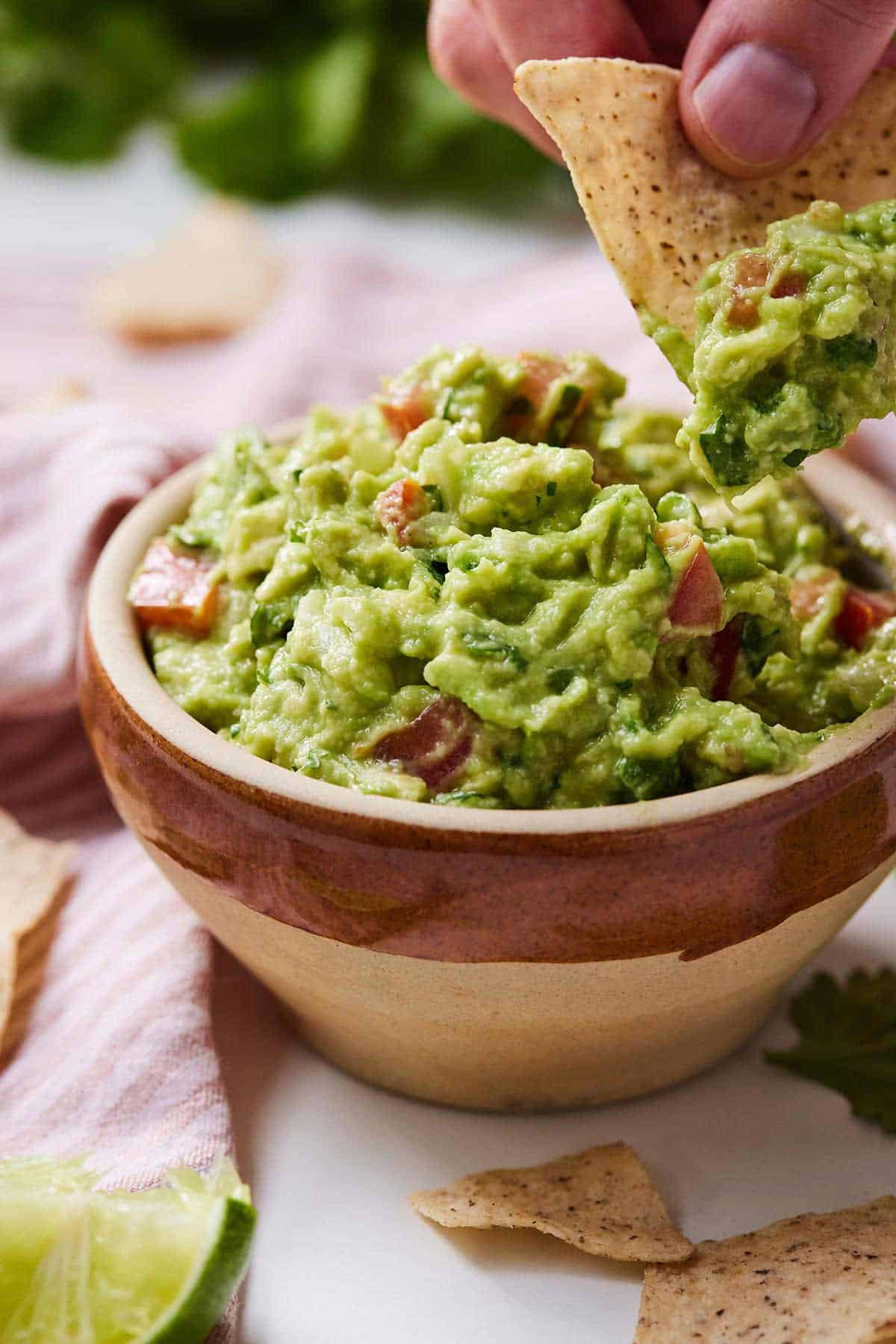 A bowl of guacamole with a tortilla chip scooping some out.
