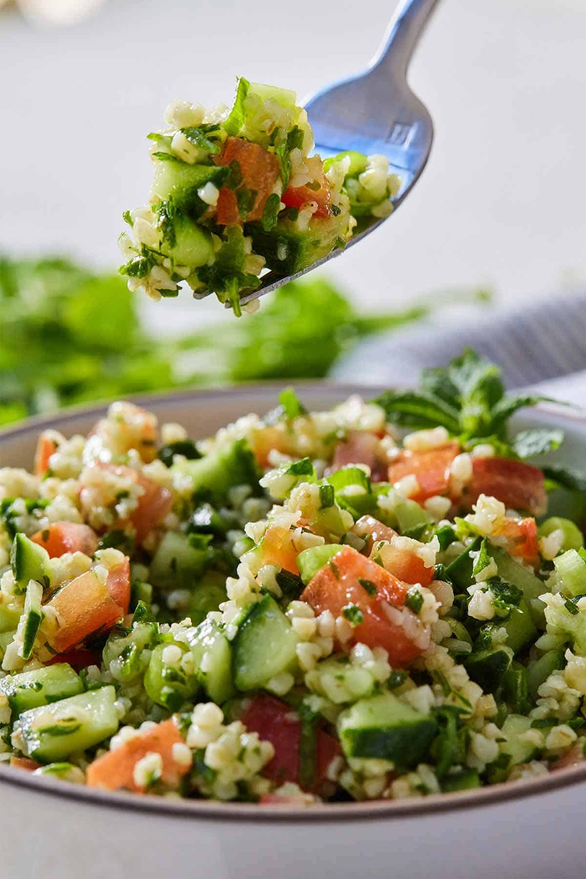 Close up of a fork lifting up a bite of tabbouleh from the bowl.