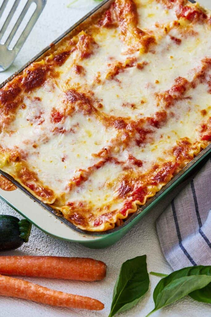 Overhead view of a dish of vegetarian lasagna beside two carrots, a zucchini, and a linen.