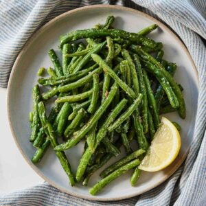 Overhead view of a plate of air fryer green beans with a lemon wedge.