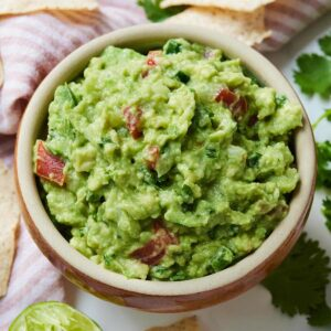 Close up of a bowl of guacamole with pieces of diced tomatoes mixed in.