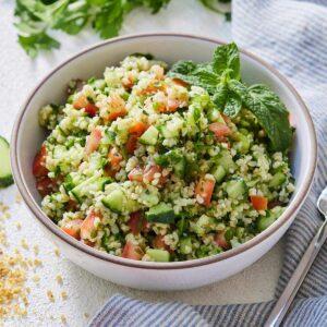 A bowl of tabbouleh beside a linen, fresh parsley, cucumbers, and bulgar.