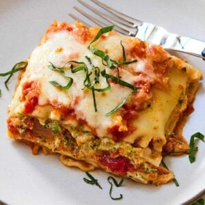 Close up of a serving of lasagna with chiffonade basil on a white plate.