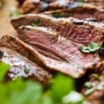 Pinterest image of an angled view of sliced carne asada with one piece in focus.