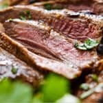 Pinterest image of sliced carne asada with one piece in focus.