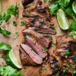 Pinterest image of the overhead view of sliced carne asada beside cilantro leaves and lime wedges.