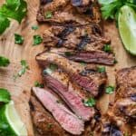 Pinterest image of the overhead view of a large carne asada, sliced, on a butcher block.