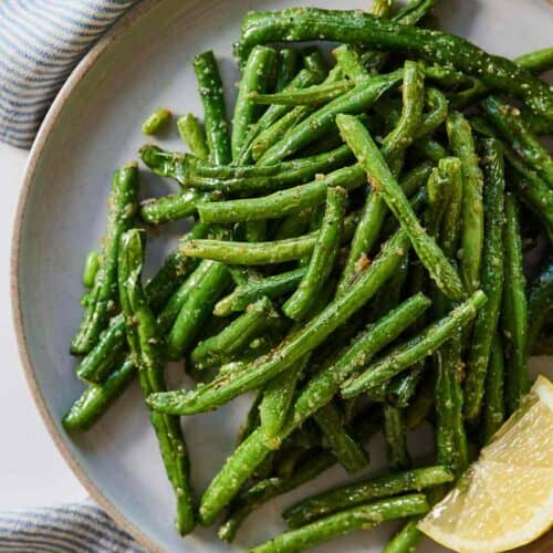 Overhead view of a plate of air fryer green beans with a lemon wedge surrounded by a blue striped linen napkin.