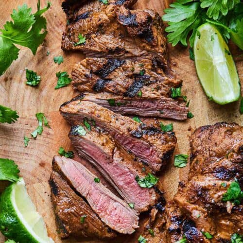 Overhead view of a sliced carne asada on a cutting board surrounded by cilantro leaves and lime wedges.